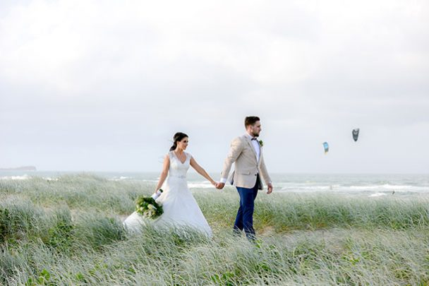 sunshine coast beach wedding photographer grassy dunes bride and groom on a windy day
