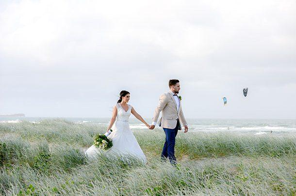 sunshine coast beach wedding photographer grassy dunes bride and groom on a windy day