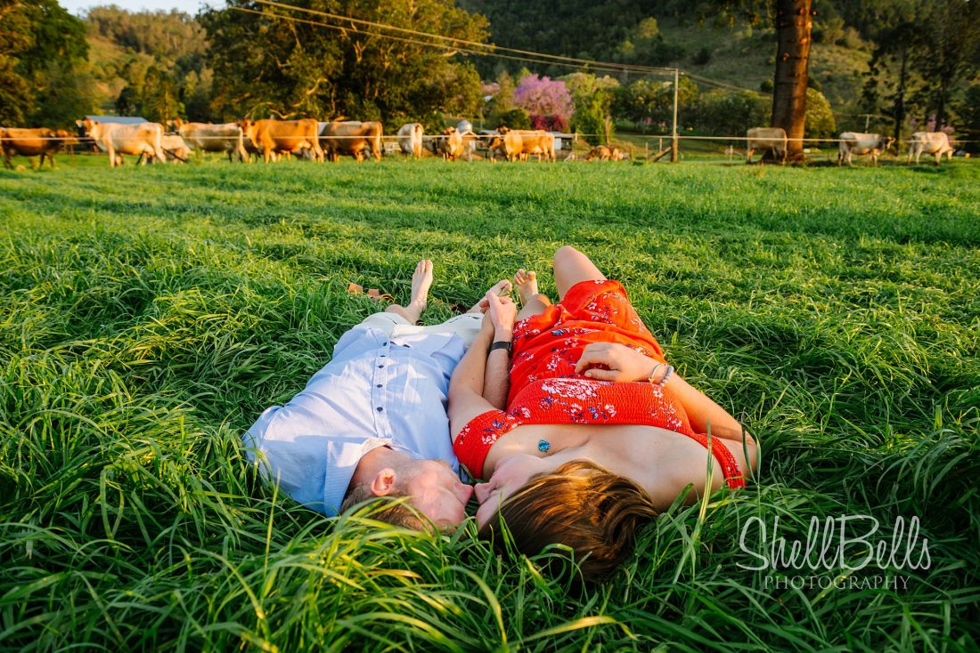 Sam & Michaella laying in the lush green grass of the Dairy Farm in Kennilworth